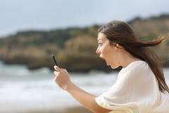 Verbaasd meisje met haar slimme telefoon Royalty-vrije Stock Afbeeldingen
