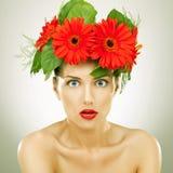 Verbaasd met rode gerbera bloeit op haar hoofd Stock Afbeeldingen