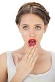 Verbaasd model in witte kleding die behandelend haar mond stelt Royalty-vrije Stock Foto's