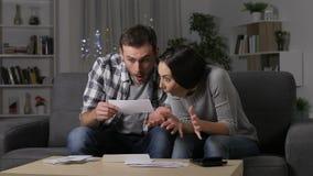 Verbaasd paar die goed nieuws bij een ontvangstbewijs lezen stock videobeelden