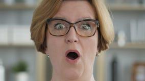Verbaasd, verrast oud hoger vrouw het benieuwd zijn gezicht stock footage
