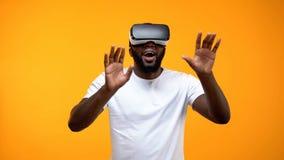 Verbaasde Afro-Amerikaanse mens die in VR-hoofdtelefoon moderne technologie?n, toekomst onderzoeken stock foto