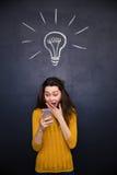 Verbaasde gelukkige vrouw die mobiele telefoon over bordachtergrond met behulp van Royalty-vrije Stock Afbeelding