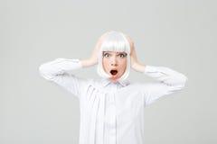 Verbaasde geschokte jonge vrouw in en blondepruik die bevinden zich gillen Royalty-vrije Stock Foto's