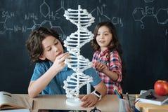 Verbaasde jonge geitjes die genetische code bestuderen op school royalty-vrije stock fotografie