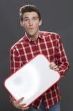 Verbaasde jonge mannelijke tiener voor publicitaire mededeling Stock Foto