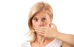 Verbaasde jonge vrouw die mond op wit behandelen Stock Afbeelding