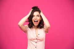 Verbaasde jonge vrouw die over roze achtergrond schreeuwen Royalty-vrije Stock Foto