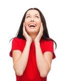 Verbaasde lachende jonge vrouw in rode kleding Stock Afbeeldingen