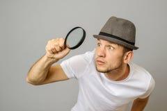 Verbaasde mens die door een vergrootglas kijken stock fotografie