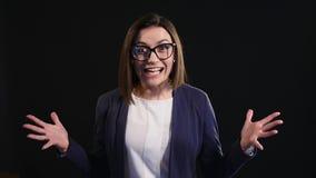 Verbaasde onderneemster die donkere achtergrond gillen stock videobeelden