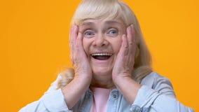 Verbaasde oude dame die gezicht behandelen door handen, die door goed nieuws, opwinding worden verrast stock footage