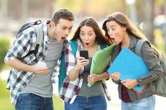 Verbaasde studenten die inhoud controleren op een telefoon stock foto's