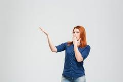 Verbaasde vrouw behandelde mond met hand en het tonen copyspace Royalty-vrije Stock Fotografie