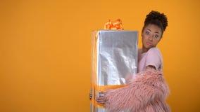 Verbaasde vrouw die grote giftbox houden, aan de dienst van de deurlevering, gele achtergrond stock footage