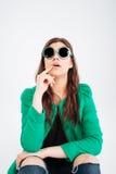 Verbaasde vrouw in ronde en zonnebril die omhoog zitten eruit zien royalty-vrije stock afbeelding