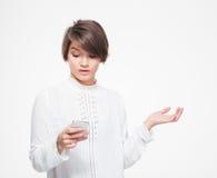 Verbaasde vrouwelijke holding copyspace op palm en het gebruiken van mobiele telefoon Stock Foto