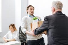 Verbaasde werknemer die de doos met bezittingen van de werkgever ontvangen royalty-vrije stock afbeelding