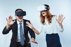 Verbaasde werknemers die virtuele werkelijkheidsglazen dragen Stock Afbeeldingen