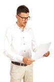 Verbaasde zakenman die aan document kijken Royalty-vrije Stock Foto's