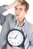 Verbaasde zakenman die in grijs kostuum een klok houdt Stock Afbeelding