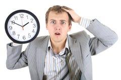 Verbaasde zakenman die in grijs kostuum een klok houdt Royalty-vrije Stock Foto