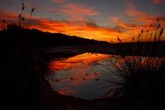 Verbazend opvlammend zonsonderganglandschap over het eiland en de hemel boven het met een ontzagwekkende zon Zonsondergangmening  stock afbeeldingen