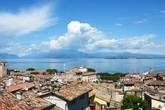 Verbazend panorama van Desenzano-kasteel op Meer Garda met oude stadsdaken, bergen, witte wolken en zeilboten op het meer, Desen Stock Foto's