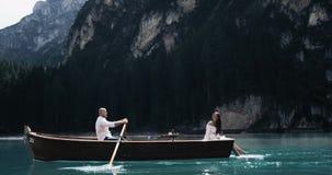 Verbazend romantisch paar in het midden van een meer in de houten boot het besteden tijd samen roeit de man stock footage