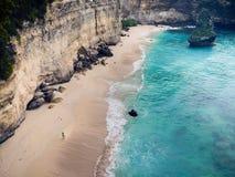 Verbazend strand met wit zand en azuurblauwe die overzees door rotsen, de mening vanaf de bovenkant wordt omringd stock foto