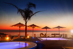 Verbazende dageraad met palm en parasols bij achtergrond met hemel Stock Fotografie
