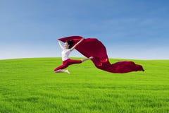 Verbazende danser die met rode sjaal op gebied springen Stock Afbeeldingen