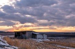 Verbazende de winterzonsondergang over bescheiden barak en landbouwgronden stock foto's