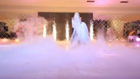 Verbazende eerste dans van gelukkige jonggehuwden De bruidegom spint zijn mooie bruid terwijl het zijn shouded door witte damp bi stock video