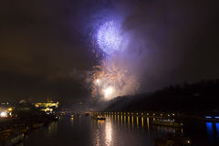 Verbazende heldere gouden en purpere vuurwerkviering van het nieuwe jaar 2015 in Praag met de historische stad op de achtergrond Stock Fotografie