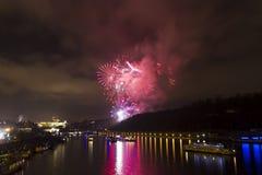 Verbazende heldere rode en roze vuurwerkviering van het nieuwe jaar 2015 in Praag met de historische stad op de achtergrond Stock Foto's