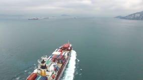 Verbazende 4k luchtmening over een schip die van de ladingsvracht langzaam in de oceaan op een bewolkte dag varen stock video