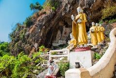 Verbazende mening van de standbeelden van partijbuddhas en godsdienstige gravure op kalksteenrots in het heilige hol van Kaw Goon stock fotografie