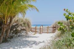 Verbazende mening van de weg van tropische tuin die door de poorten naar wit zandstrand en azuurblauwe rustige oceaan leiden Stock Foto's