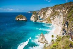 Verbazende mening van een geheim strand met kokospalmen en rotsen in Nusa Penida, Bali stock foto