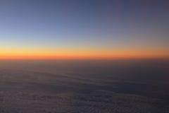 Verbazende mening van vliegtuig op de hemel, de zonsondergangzon en de wolken Stock Foto's