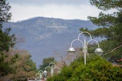 Verbazende mooie mening van bergen met inschrijving ?Gelendzhik ?van stadssteeg met mooie lantaarns en groene bomen royalty-vrije stock afbeelding