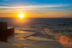 Verbazende oceaanzonsondergang bij de steenpijler in kalm weer nave Royalty-vrije Stock Foto's