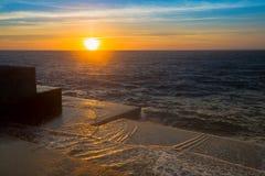 Verbazende Overzeese zonsondergang bij de steenpijler in kalm weer nave Stock Foto's