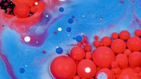 Verbazende rode en blauwe bellen van verf op de olieoppervlakte Verf in olie stock footage