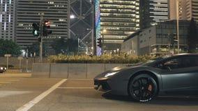 Verbazende sportwagen in stad bij het verkeerslicht bij nacht voorraad Nachtmening van de sportwagen bij het verkeerslicht stock videobeelden