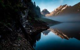 Verbazende waterbezinning in duidelijk moutainmeer tijdens zonsopgangochtend Zwitserland stock afbeelding