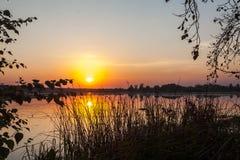 Verbazende zonsondergang over het meer Kleurrijke bezinning in het water royalty-vrije stock foto