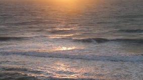 Verbazende zonsondergang over het strand De overzeese strandgolven op strand in zonsondergangtijd, zonlicht overdenken waterspieg stock footage