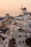 Verbazende Zonsondergang over witte windmolens in stad van Oia en panorama aan Santorini-eiland, Thira, Griekenland Stock Foto's